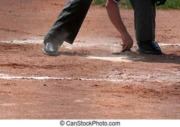 Dusting off the Plate - An umpire dusts off home plate.