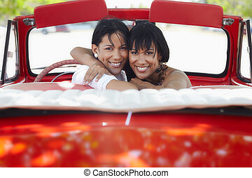 beautiful twin sisters hugging in cabriolet car - young...