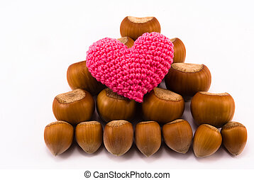 pink heart and hazelnuts of different sizes in the form of a...