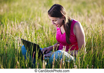 pretty , young woman using her laptop computer outdoors in...
