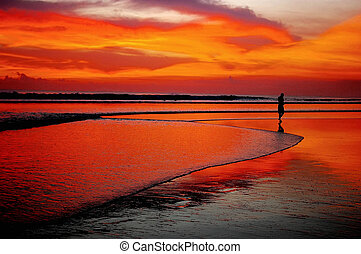 Lone man on beach at sunset - Lone man at sunset on beach,...