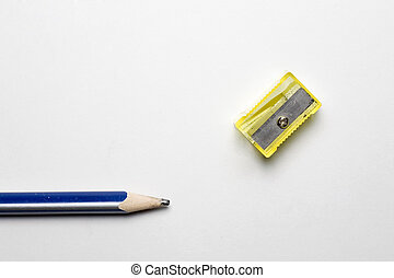 pencil and sharpener - a pencil sharpener next to a blue...