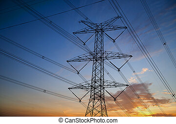 Electricity pylon with many cables at sunset