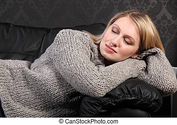 Beautiful blond woman asleep in grey knit sweater