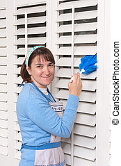 Woman cleaning shutters - A woman dusting her dirty window...