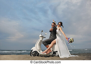 just married couple on the beach ride white scooter -...
