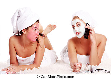 Two beautiful girl relaxing in spa with nutrient facial...