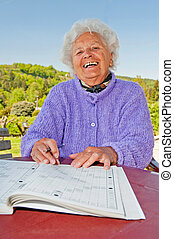 Senior Woman Doing a Crossword - Portrait of a senior woman...