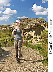 Hiker in badlands of Alberta, Canada - Smiling girl walking...