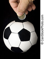 Soccer investment - A coin is deposited into a piggy bank...