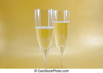 Two champagne flutes with golden background and copy space