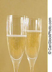 Two champagne flutes with golden background