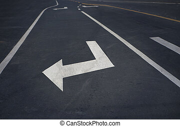Arrow sign on asphalt indicatng a turn
