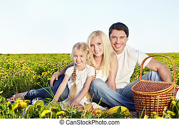 Picnic - A happy family with a child at a picnic in a field