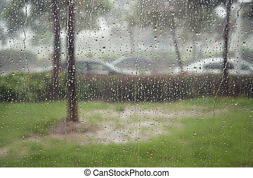 Glass window in rain storm - trees and some cars seen...