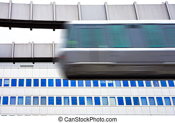 Sky-Train passing fast in front of office building