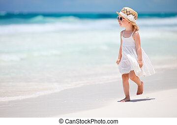 Little lady at beach - Adorable little girl walking along...