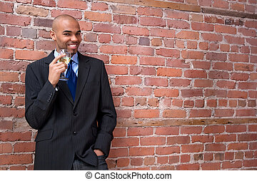 Young business man drinking wine and smiling - Young...