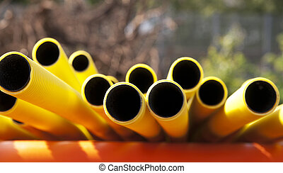 Yellow plastic pipes in sunshine