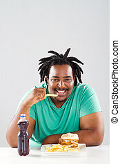 african american man eating chips - overweight african...