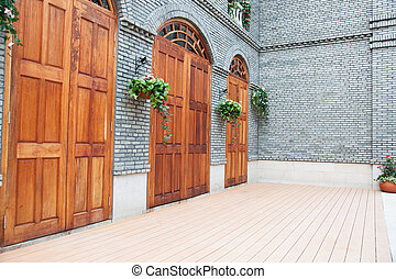 Traditional Chinese house with wooden arch doors and deck. -...