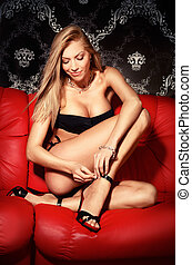 Sexy young blonde lady in black lingerie on red leather sofa
