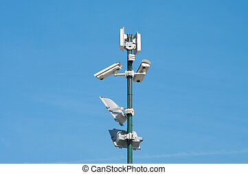 security cameras and floodlights mounted high on a pole to...