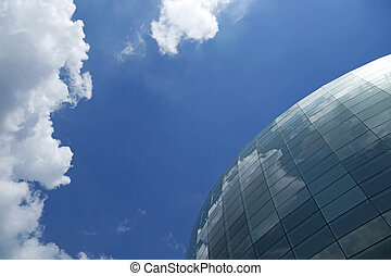 Spherical glass facade reflecting the blue sky and white...