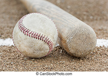 A baseball and baseball bat in a field