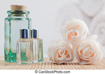 Roses and glass flasks with white towels on the background