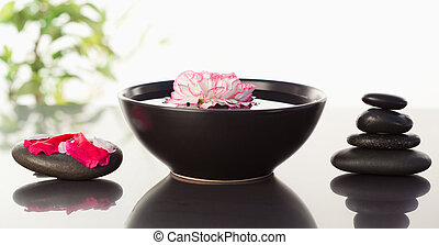 Pink carnation floating in a bowl with petals on a black stone on one side and a stack ok black stones on the other side