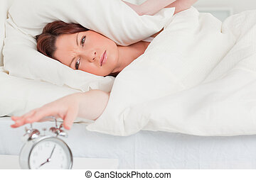 Charming red-haired woman waking up thanks to an alarm clock