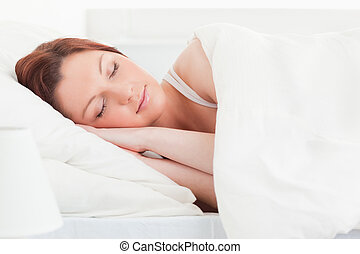 Close-up of a good looking red-haired woman sleeping in her...