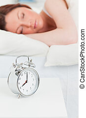 Attractive red-haired woman sleeping in her bed