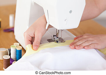 Caucasian hands using a sewing machine in the living room