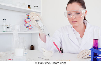 Beautiful red-haired scientist using a pipette in a lab