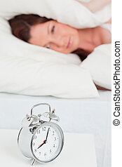 Beautiful red-haired woman waking up thanks to an alarm clock