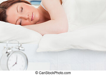 Charming red-haired woman sleeping in her bed