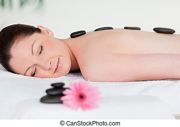 Young woman having a black stones massage
