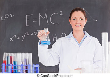 Cute scientist holding a container filled up with a blue...