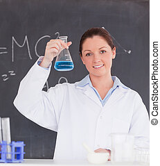 Beautiful scientist showing a container filled up with a...