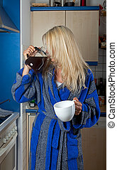 sleepy blonde woman drinking coffee from the pot