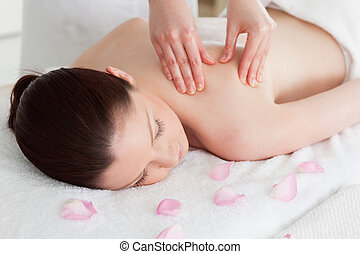 Beautiful woman having a back massage surrounded by petals