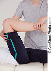 Portrait of a masseuse stretching the right leg of an athletic woman