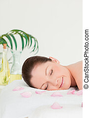 Portrait of a young woman lying on a massage table with...