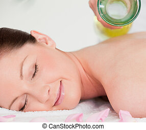 Smiling young woman having massage oil versed on her back in...