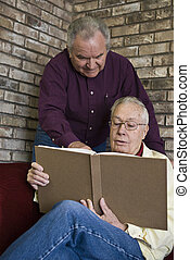 Adult literacy - Senior adult men read together.