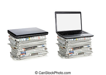 stack of newspaper and laptop