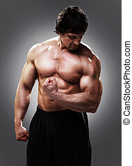Bodybuilder showing his biceps - Bodybuilder showing his...