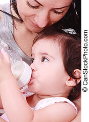 Mother and baby drinking milk from bottle in a white...